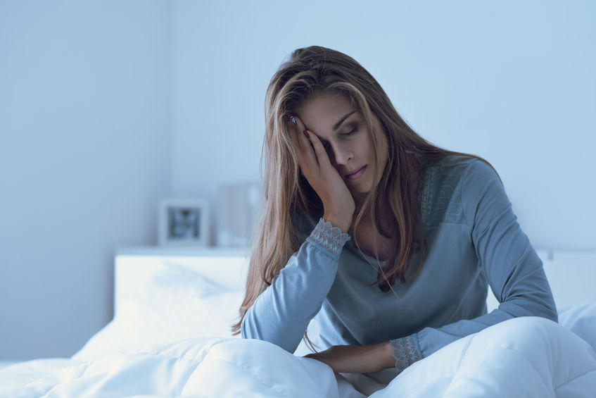 Depressed woman awake in the night, she is touching her forehead and suffering from insomnia
